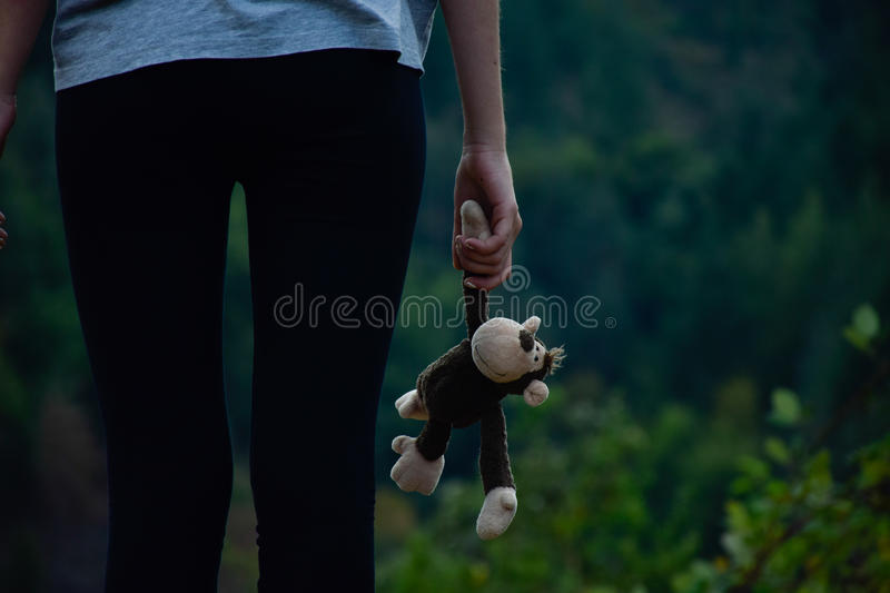 Rear view of girl, close up of hands of a female child holding a monkey toy. Girl standing holding a brown furry monkey toy. Monkey toy and girlhand. Girl royalty free stock image