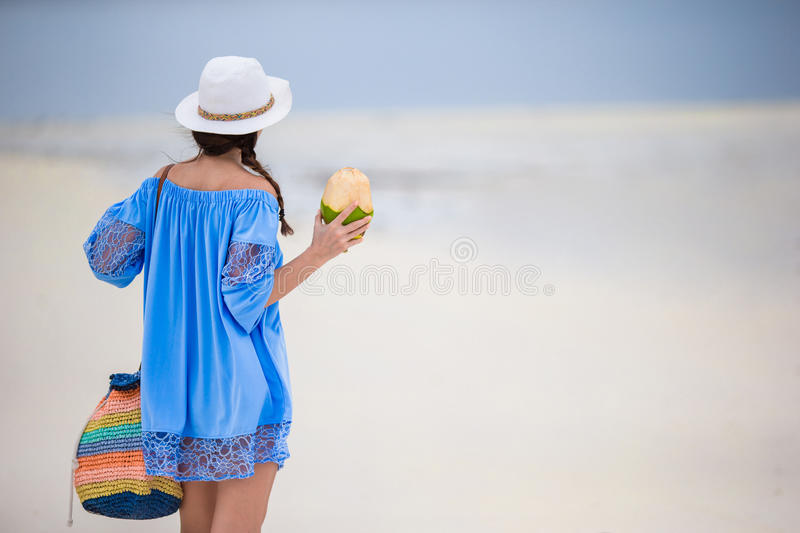 Rear view of girl drinking coconut milk during tropical vacation stock photos