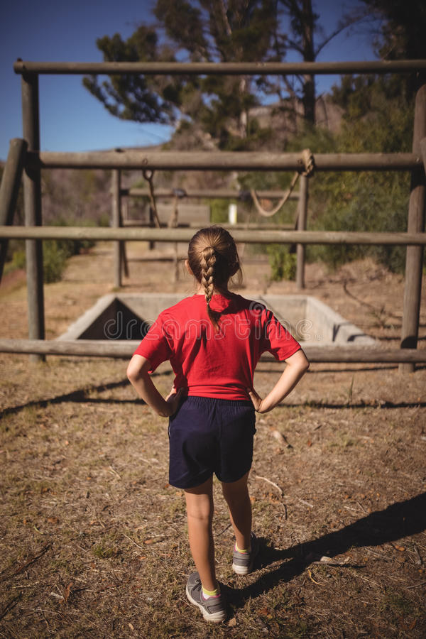 Rear view of girl looking at outdoor equipment during obstacle course royalty free stock photo