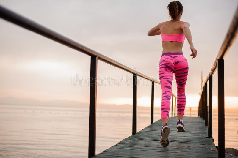 Rear view girl running to the new life on the sunrise. Ready to achieve a new goal. Conception of the healthy lifestyle stock photo