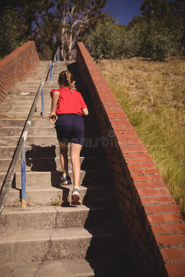 Rear view of girl running upstairs during obstacle course stock photography