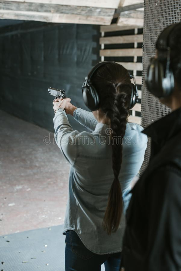 rear view of girl shooting with gun stock images
