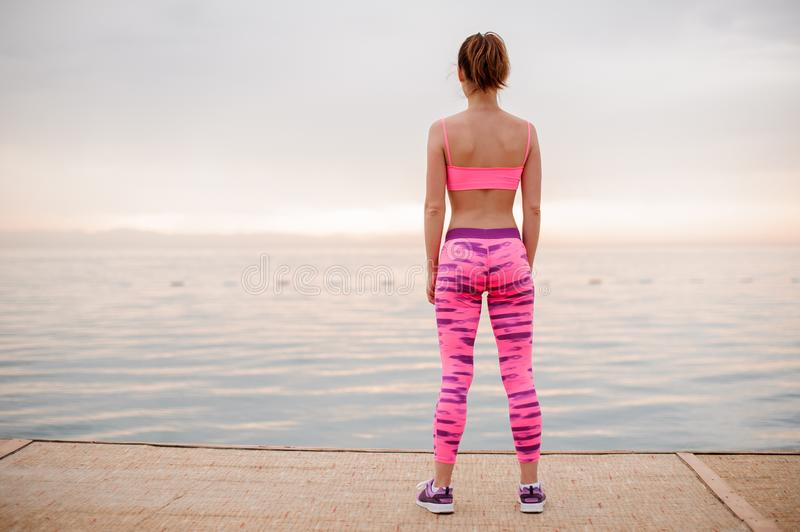 Rear view girl standing on the seaside and looking at the new life. And ready to a goals achievement.Conception of the healthy lifestyle stock photos