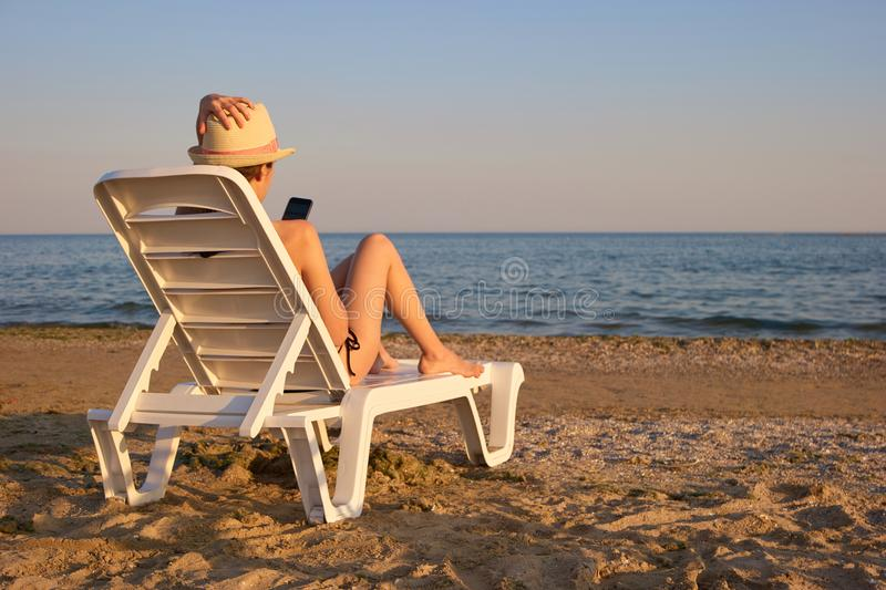 Rear view girl using smartphone lying on the beach chaise longue. royalty free stock images