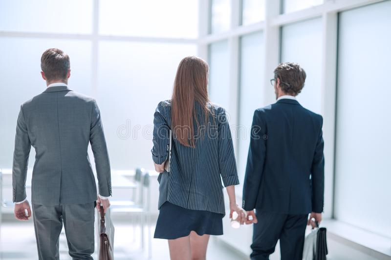 Rear view.a group of business people walking down the office corridor . stock image
