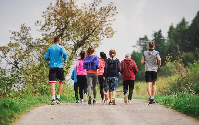 Rear view of group of multi generation people running a race competition in nature. Rear view of group of active multi generation people running a race stock photos
