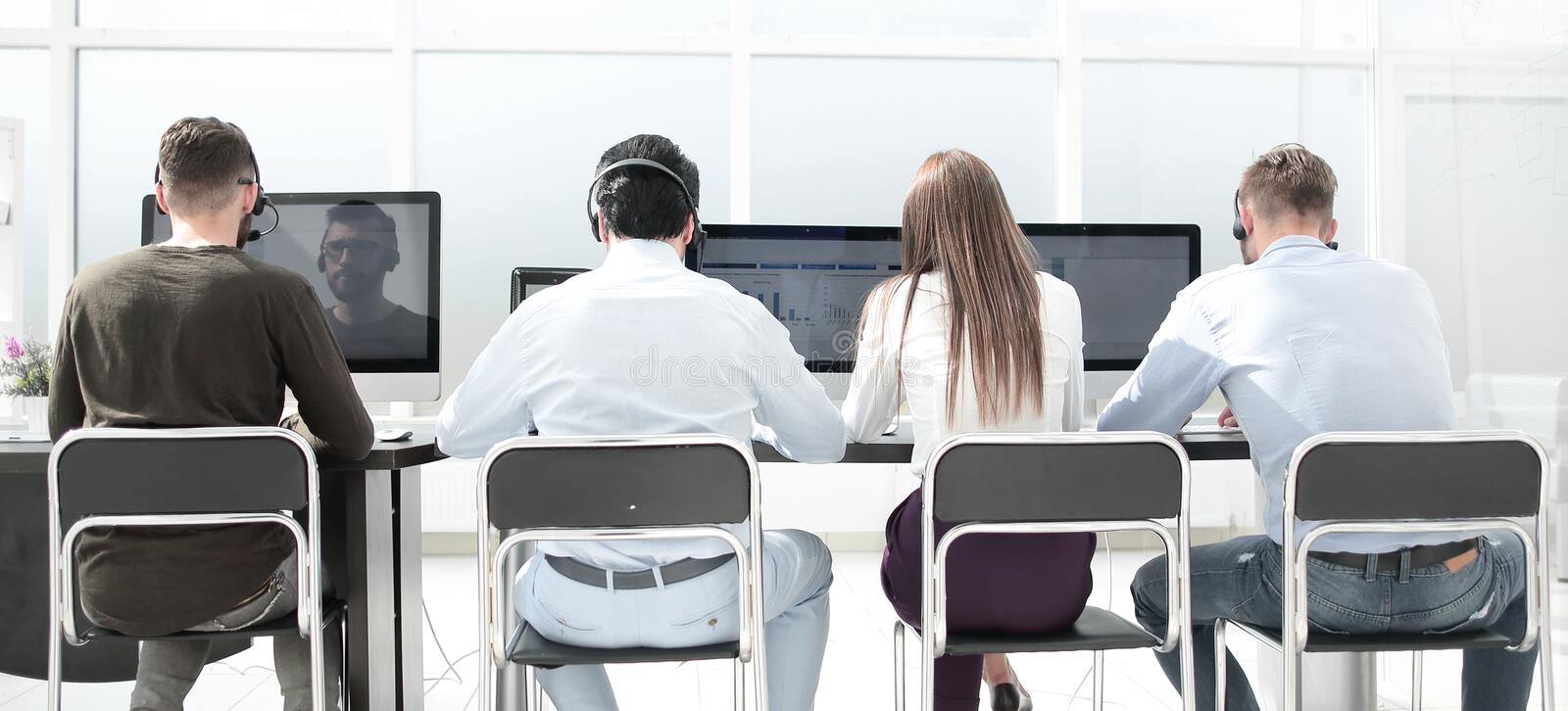 Rear view.a group of people in the headset works in a modern office. stock photo