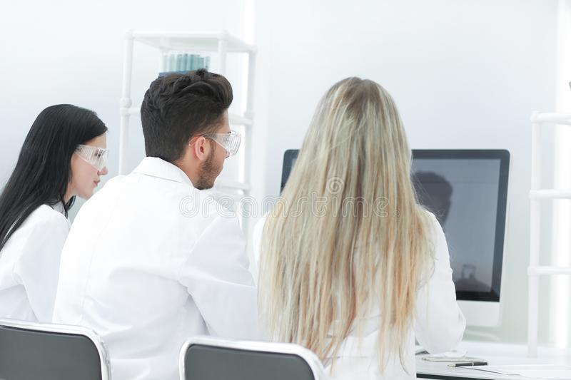 Rear view.a group of scientists look at the computer monitor stock image