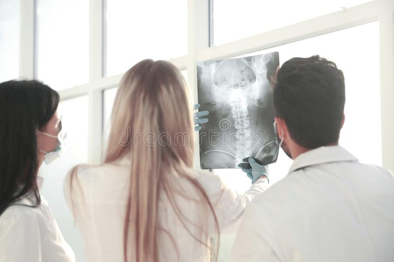 Rear view. a group of surgeons discussing x-ray stock photo