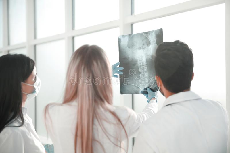Rear view. a group of surgeons discussing x-ray stock images
