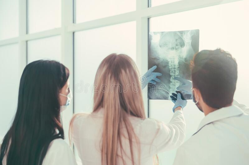 Rear view. a group of surgeons discussing x-ray stock image