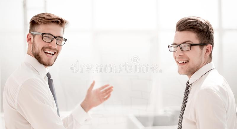 Rear view.happy business colleagues standing in a bright office royalty free stock images