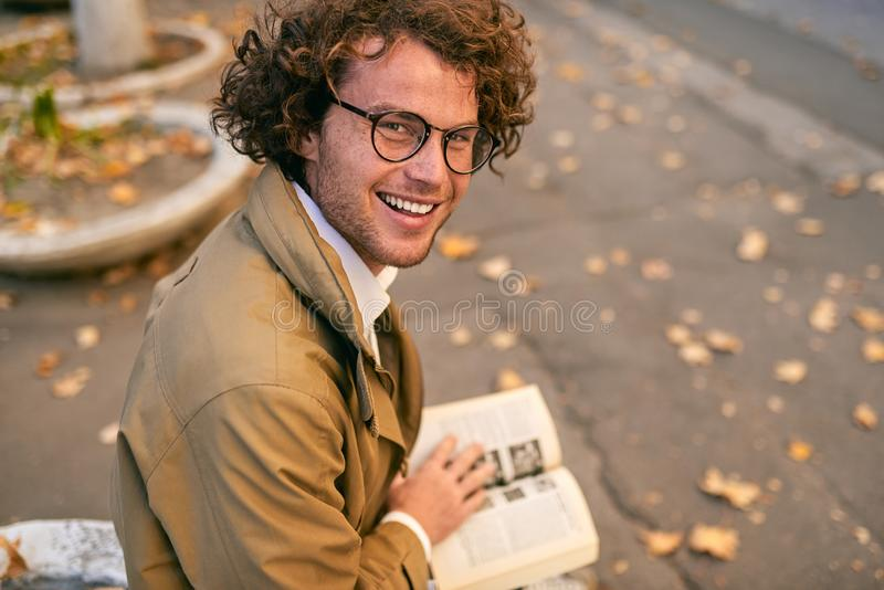 Rear view of happy handsome young man reading book outdoors. College male student carrying books in campus in autumn street. Smiling smart guy wears spectacles stock photos