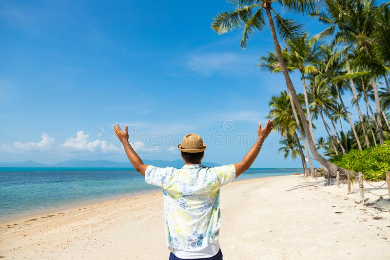 Rear view happy young asian man on the tropical beach. stock photos