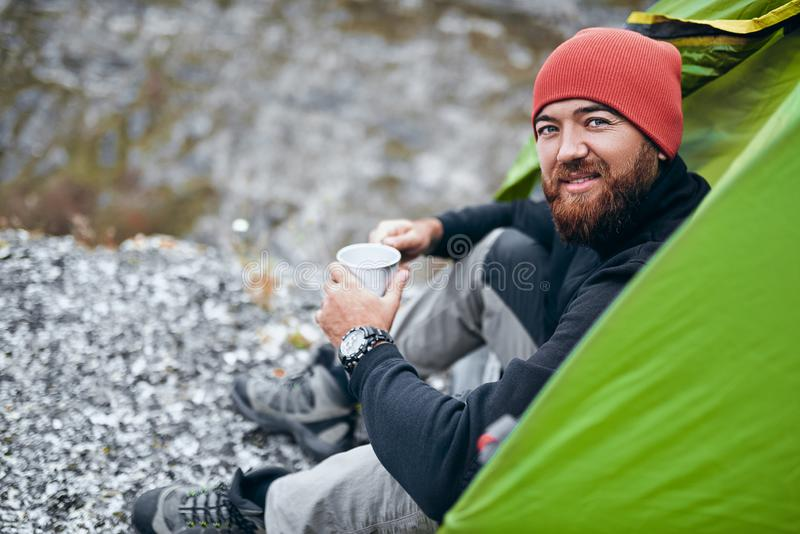 Rear view of happy young male drinking hot beverage in mountains. Traveler man with beard wearing red hat, sitting near to camping royalty free stock photos