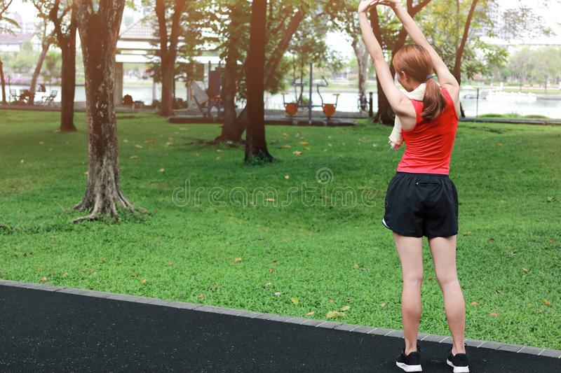 Rear view of healthy young Asian woman stretching her hands before run in park in morning. Workout and exercise concept. stock image