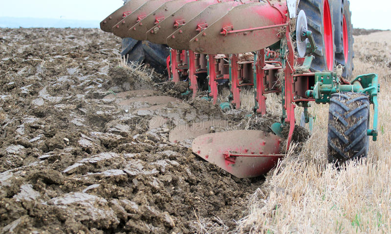 Rear view of heavy plough or plow. A rear view of a plough or plow plowing and turning over the stubble of crops into earth to plant crops. Being pulled by a stock photo
