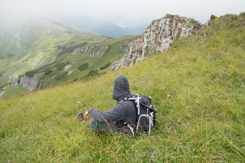 Hiker sitting on grass in mountains stock photos
