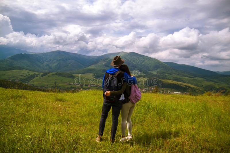 Rear view of hiking couple hugging and laughing on top of mountain. Beautiful nature of the mountains and hill in summer stock photography
