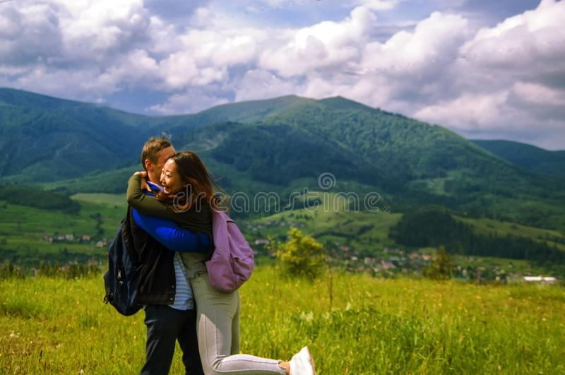 Rear view of hiking couple hugging and laughing on top of mountain. Beautiful nature of the mountains and hill in summer stock images