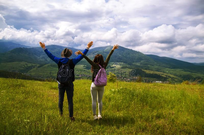 Rear view of hiking couple hugging and laughing on top of mountain. Beautiful nature of the mountains and hill in summer royalty free stock photos
