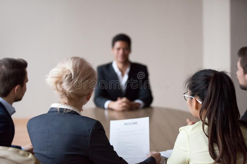 Rear view of hr listening to applicant at job interview. Rear view of hr managers group listen to african male applicant at job interview, recruiters employers stock image