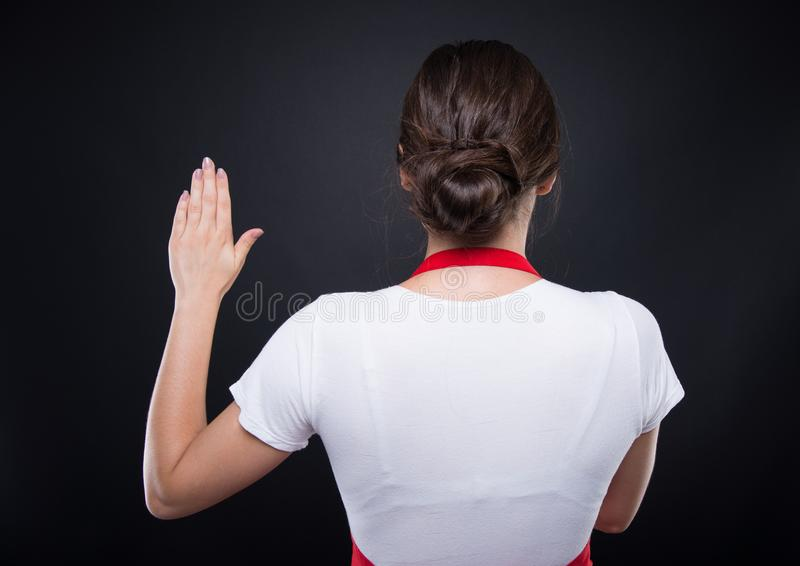 Rear view of hypermarket employee making a promise. Or telling the truth royalty free stock photography