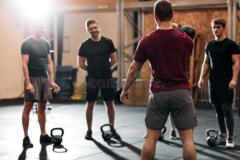 Men talking together before a strengthening class at the gym stock photography