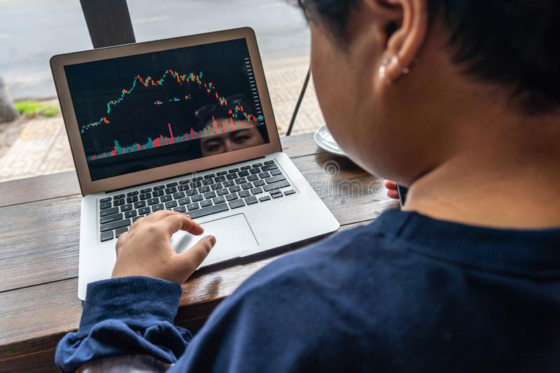 Rear view of investor watching financial candlestick graph on laptop stock image
