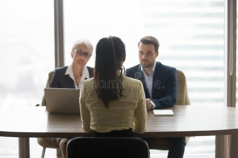 Rear view of job applicant talks to recruiters at interview. Rear view of female job applicant talking to recruiters listen at job interview, women vacancy stock photo