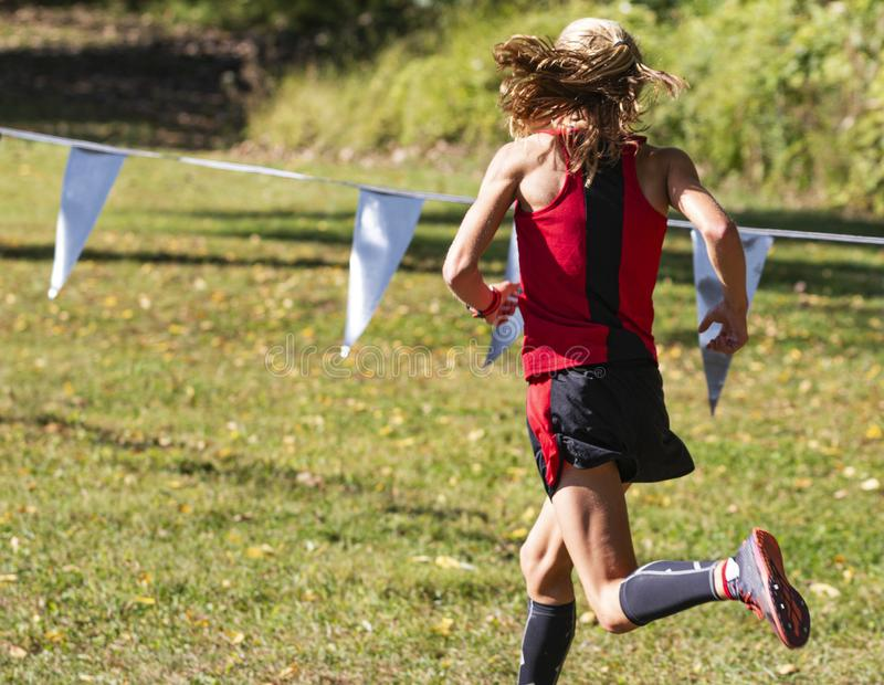 Rear view of leader of 5K cross country race on the grass stock photo