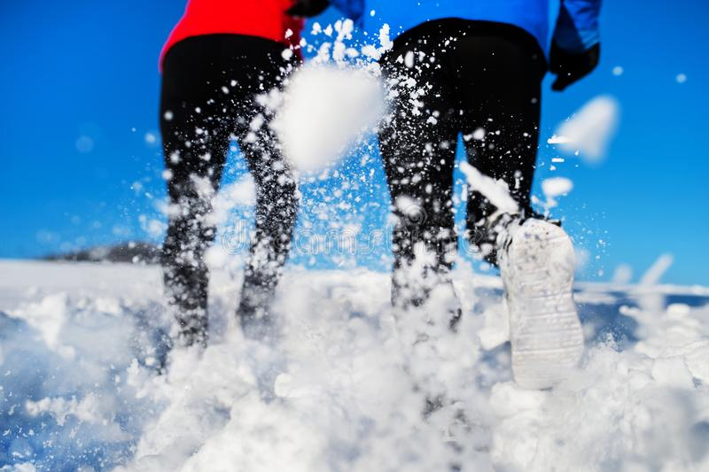 Rear view of legs of senior couple jogging in winter nature. royalty free stock image