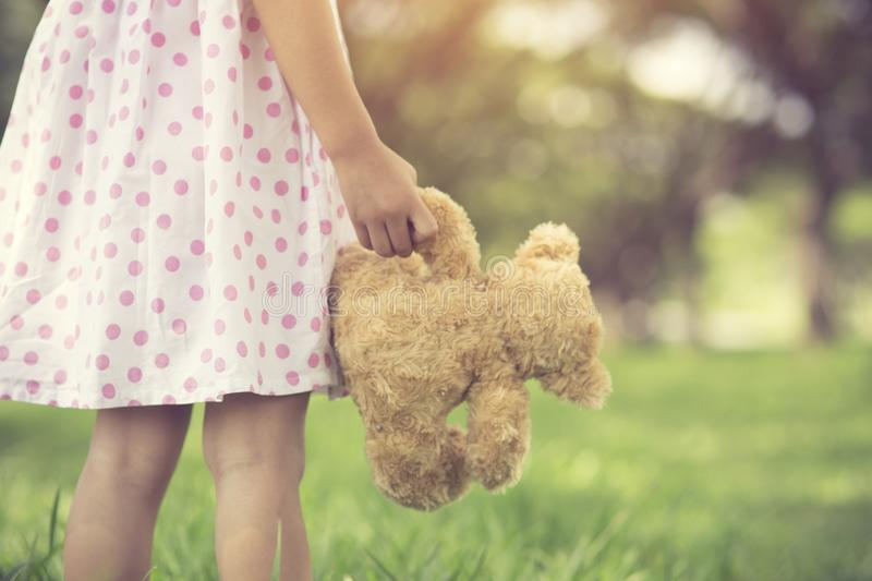 Rear view of little girl looking her future.Close up of hands of a female child holding a teddy bear. stock image
