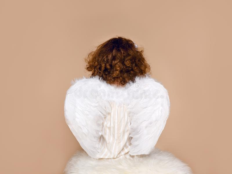 Rear view of a little girl in wings, wearing in dress seated in studio, over beige background. Valentine`s day. Cupidon. royalty free stock photo
