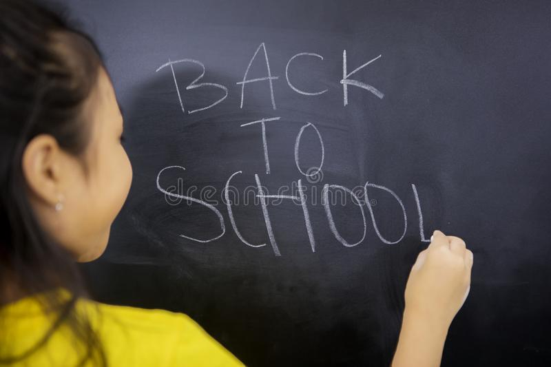 Rear view of little girl writing text of back to school royalty free stock photography