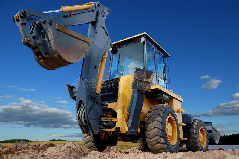 Rear view of Loader excavator with rised backhoe stock photos