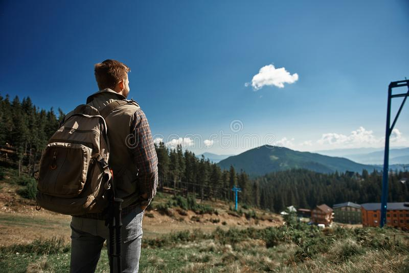Rear view of a male backpacker enjoying mountain landscape stock images