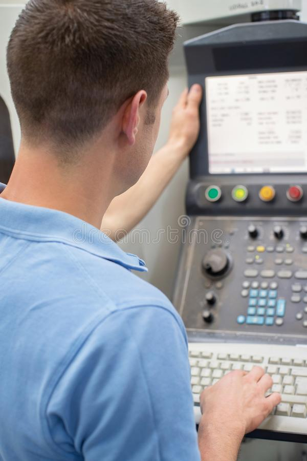 Rear View Of Male Engineer Operating CNC Machine In Factory royalty free stock photo