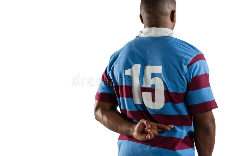 Rear view of male rugby player with fingers crossed. Standing against white background royalty free stock photography