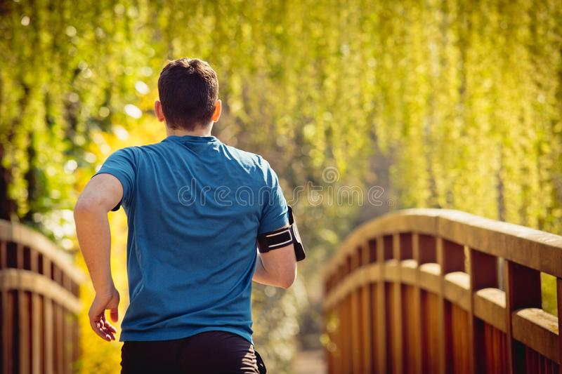Rear view Male runner running in a city park over  bridge. Training for fitness. Healthy lifestyle concept. Workout jogging activity, dynamic runner athlete royalty free stock photo