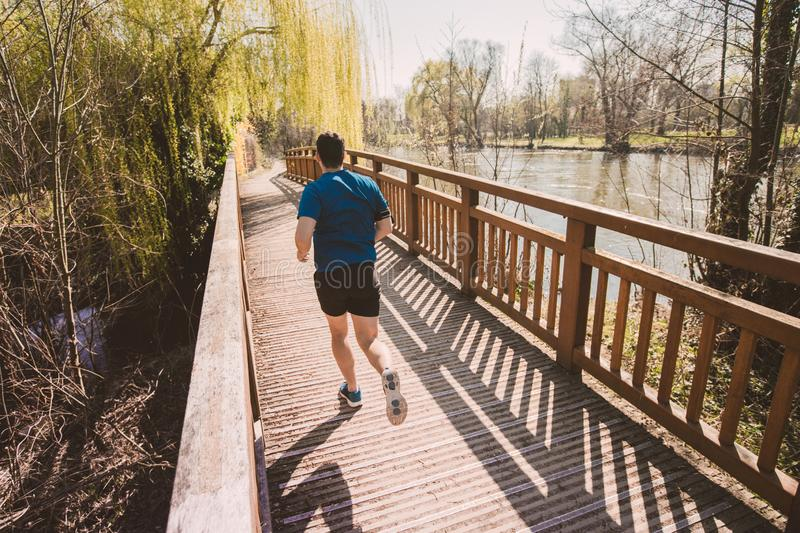 Healthy lifestyle concept. Rear view Male runner running in a city park over  bridge training for fitness. Healthy lifestyle concept. Workout jogging activity royalty free stock photo