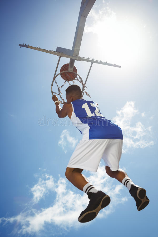 Rear view of male teenager hanging on basketball hoop. Against blue sky stock photography