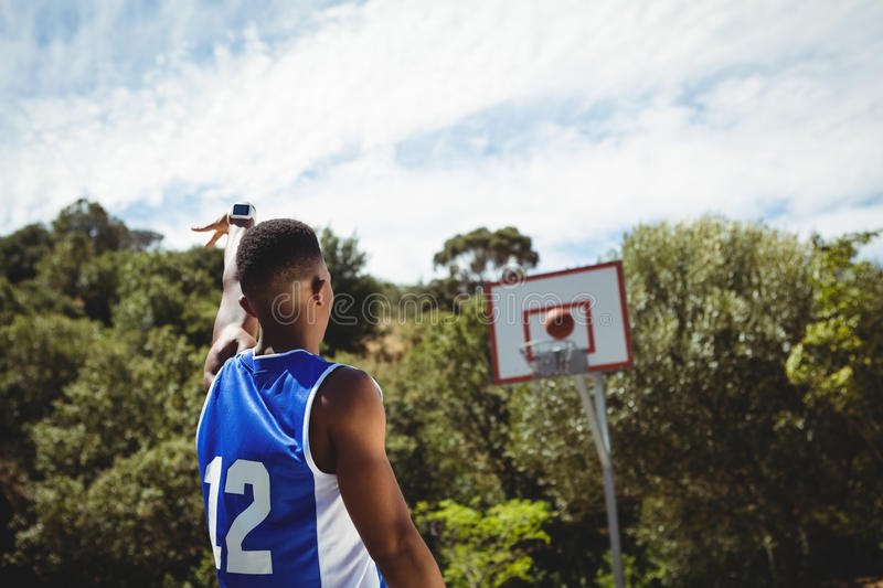 Rear view of male teenager practicing basketball. In court on sunny day stock image