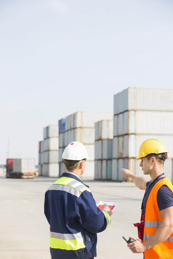 Rear view of male workers discussing in shipping yard royalty free stock photography