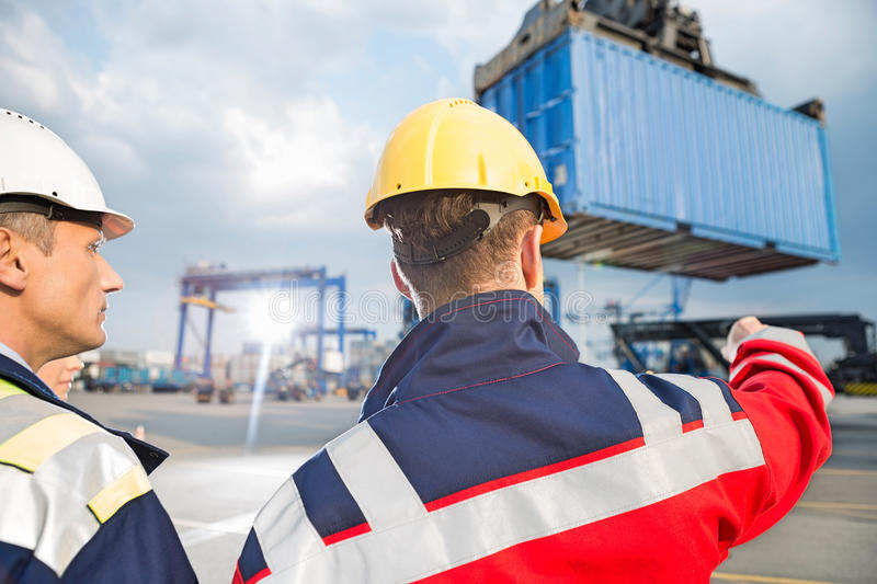 Rear view of male workers discussing in shipping yard royalty free stock images