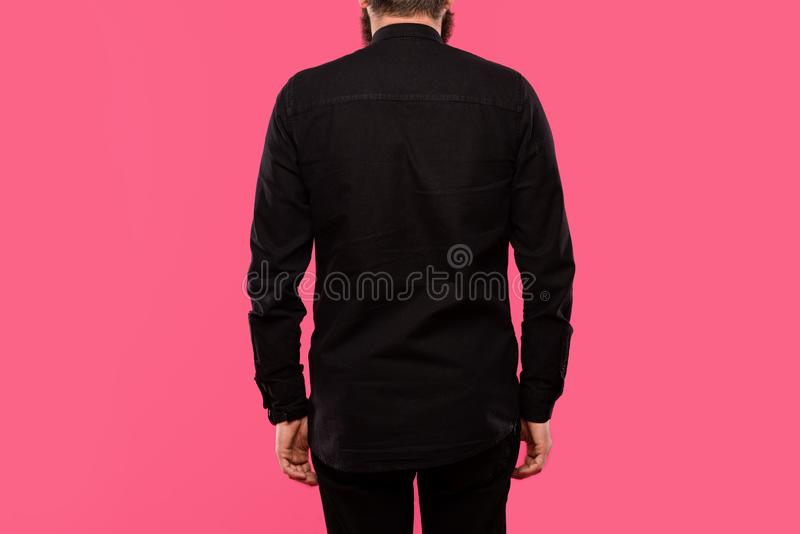 Rear view of man in black stylish shirt posing isolated. On pink royalty free stock image