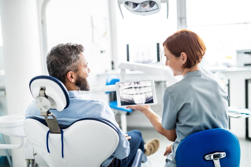 Rear view of man and dentist in dental surgery, annual check-up. A rear view of man and dentist in dental surgery, annual check-up royalty free stock photography
