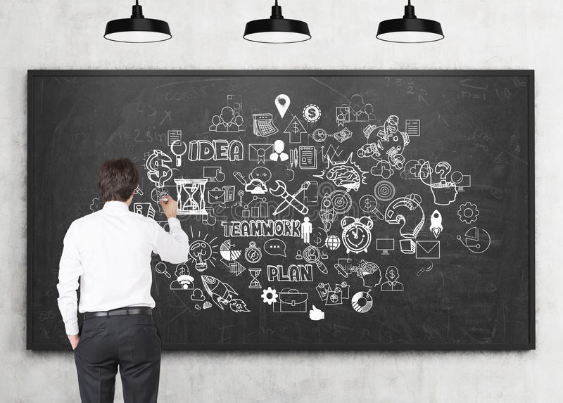 Rear view of man drawing business idea sketch. Rear view of a young businessman drawing a business idea sketch on a chalkboard in a classroom. Concept of stock image