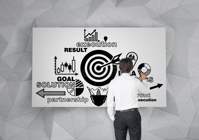 Rear view of man drawing target sketch. Rear view of a young businessman in a white shirt drawing a target poster on a wall with geometric pattern on it royalty free stock photo