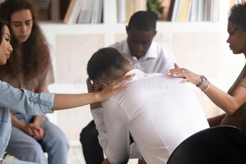 Rear view at man getting psychological support during therapy session. Rear view at upset men in trouble get psychological support during therapy session stock images